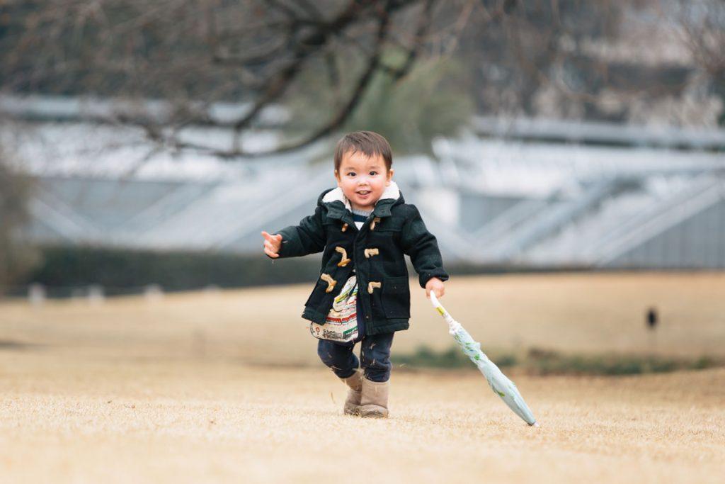 お気に入りの傘を持って嬉しそうに走る男の子