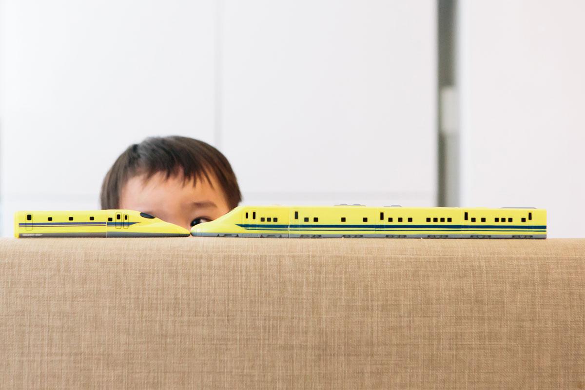 大好きな電車のおもちゃを覗く男の子