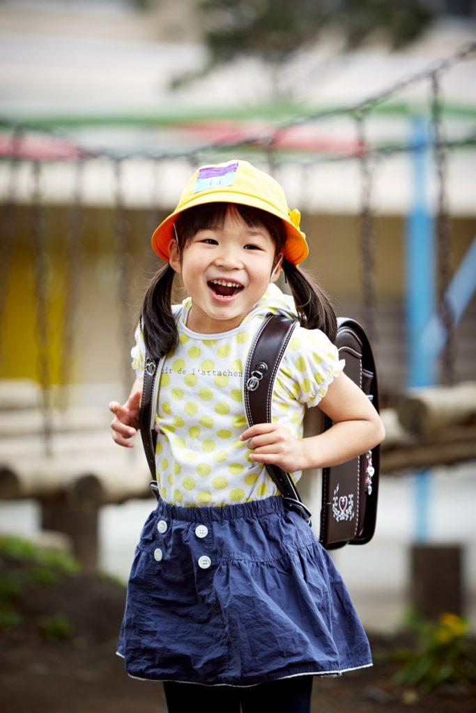 ランドセルと黄色い学生帽で笑顔の女の子