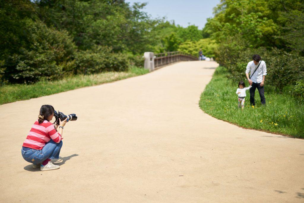 長いレンズで撮影している女性カメラマン
