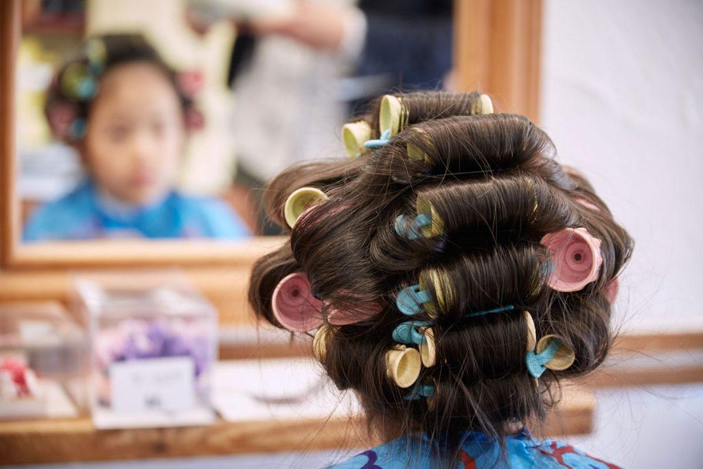 美容院で七五三用の髪の毛のセットするお姉ちゃん