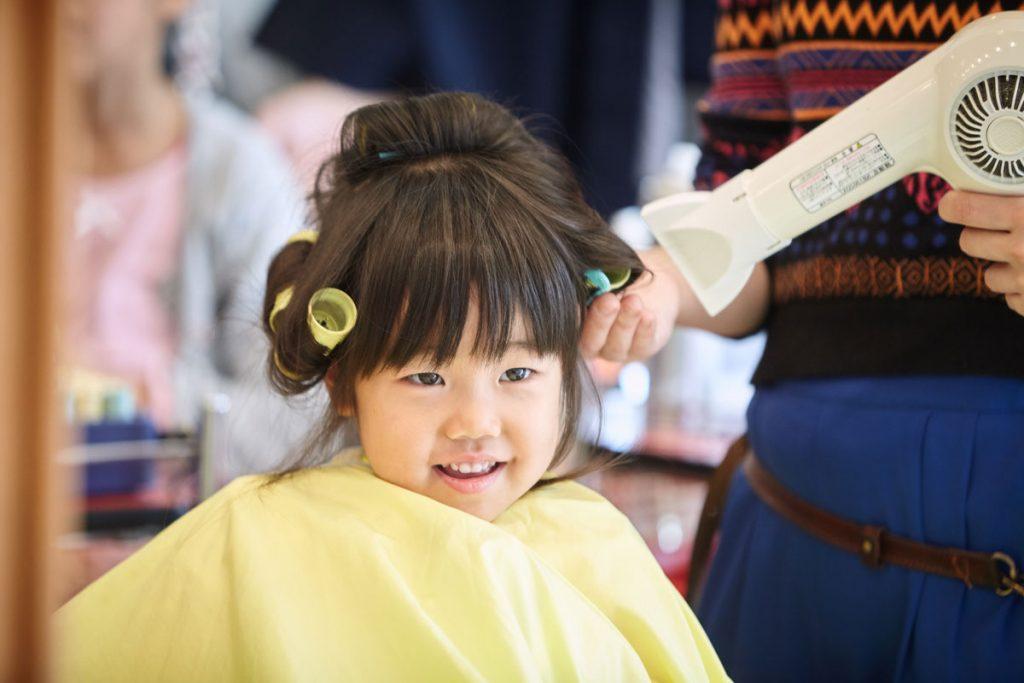 美容院で七五三用の髪の毛のセットする妹